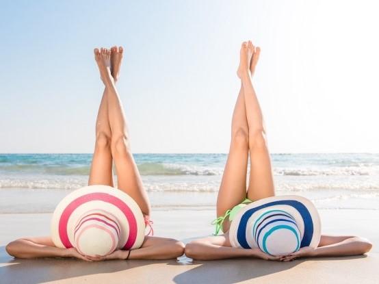 Mujeres con piernas elevadas en la orilla del mar